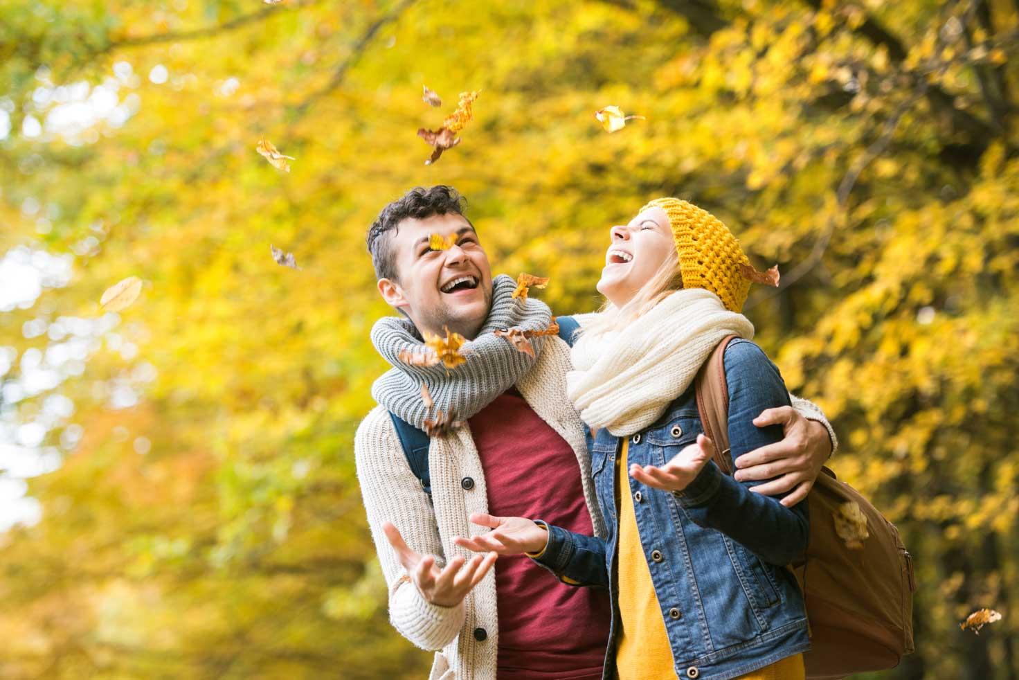 Couple enjoying autumn leaves